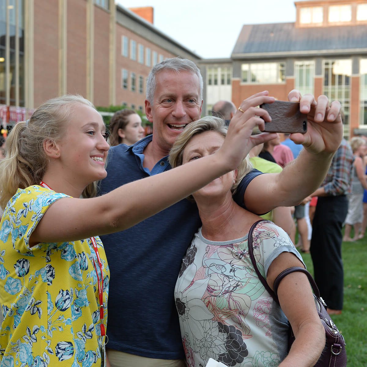 A mother, father, and daughter taking a selfie with a cellphone during Move In Day at im体育官网.